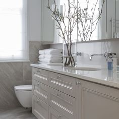 Modern grey bathroom with vase full of budding branches