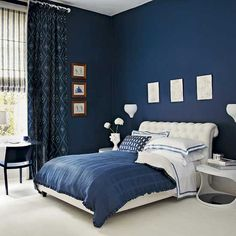 Navy blue bedroom with blue patterned curtains and white upholstered bed