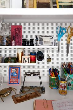 Container Stories - the elfa board gives an easy way to hang up shelves or objects. Note the pen and pencils are in old tins... familiar!