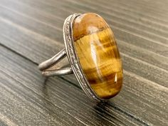 """Vintage sterling tigers eye tiger eye gemstone ring antique fine jewelry gift for herDetails:Oval tiger eye cabochon ringSterling silver settingUnmarked but tested sterlingLooks handmadeC 1970sMeasurements:US ring size 6 on the mandrelface of the ring is about 1"""" by 1/2"""" by 1/2""""Condition:Excellent vintage condition with lightest signs of age-appropriate use and wear. No damage or flaws noted.Have a question? Please send me a message! my shop:www.etsy.com/shop/mygildedmagpiemy…"""