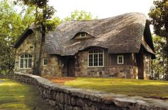 Love the curvy roof and the eyebrow window and the low stone wall  traditional exterior by Dungan Nequette Architects