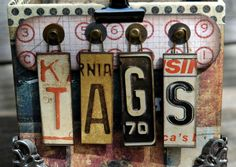 "The ""TAGS"" was created out of Tim Holtz' Destinations Salvage Stickers, some laundry pins, Tim Holtz washers and long fasteners."