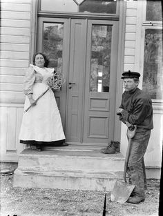 Portrait of a maid and a worker outside a building. Photographer: Paul Stang.