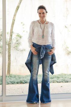 Jeans com jeans, adoro essa mistura! O jeans é um tecido que nunca   sai de moda e fazer sua própria combinação com ele mesmo fica super   autoral. Aqui usei uma calça flare com uma bata branca soltinha de algodão   e amarrei uma camisa na cintura, também jeans como a calça, o que deixa o   look descontraído. Fiz um mix de colares longos e curtos que ficasuper   moderno. Escolhi uma sandália alta de tira colorida da mesma cor que a   pedra de um dos meus colares longos. Por ser alta e de…