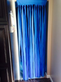 "For the shark ""under the sea"" theme birthday party, we took cheap dollar store table covers (light blue and dark blue) and cut them, leaving about 8 inches at the top to attach to the doorway. (Also helps to keep some balloons in the room)"