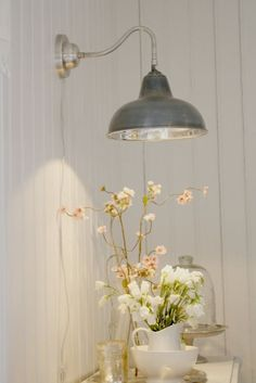 Love the galvanized tin barn light over a side table, accented with white painted wood and ceramic