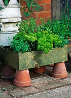 Pot Feet. It can't get simpler than this: Terra-cotta flower pots are turned upside down to hold wooden crates full of herbs.