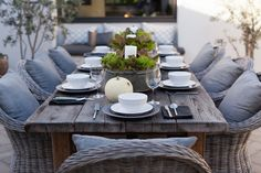 Rustic wooden tale, grey cushions, rattan chairs, outside eating!