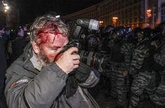 Reuters photographer Gleb Garanich, who was injured by riot police, continues shooting pictures as police scuffle with protesters during a demonstration in support of EU integration in Kiev (November 2013)