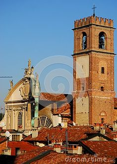 Photo made at the cathedral of Vigevano near Pavia in Lombardy (Italy). In the picture, taken from the castle, you can see part of the facade and roof and bell tower of the city's basilica. The cathedral and the bell seem to appear on the roofs of many homes to raise himself in Bluu sky.