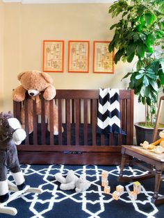 This modern nursery uses a neutral patterned wallpaper to provide a beautiful contrast to a dark wooden crib and black-and-white area rug. A rocking chair and bright orange framed wall hangings provide the finishing touches.