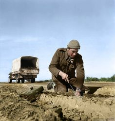A Sapper from the Royal New Zealand Corps of Engineers probes at the earth in the search for more mines after lifting (digging out) a German Tellermine, near Tripoli, Libya, on the 22d of January, 1943.