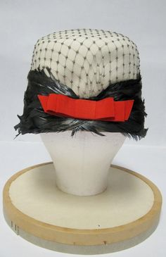 1960's Ivory Felt Hat with Black Netting Steel Colored Feather Detail and Red Grosgrain Bow in Back. $80.00, via Etsy.
