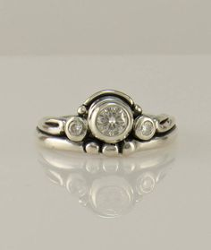 R1135- Sterling Silver Ring with a a 4.5 mm and 2) 2.5 mm Classic Moissanites, Size 7 1/4. I can size it to fit, just contact me. No charge to size down. Convo me on sizing up. The top of the ring measures 9 mm and the band is 2 mm. All of my pieces are One of a Kind. This ring is made by the Lost wax Casting method, where I make the design in wax and then cast it into silver. To learn more about Me and the Lost Wax Method please visit my website at www.denimanddiamondsjewelry.com Th...
