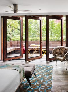 """In Tia Cibani's master suite, the architect created a sizable terrace. The wood floors within the room run right out of doors, establishing a subtle sense of continuity. Thus, says Dubbeldam, """"the balcony becomes part of the bedroom."""" The coin chair is by Johnny Swing. The bed is from Design Within Reach."""
