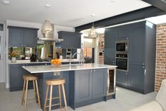Modern shaker kitchen in dark slate blue looks stunning against the brick wall. The cabinets are complemented by marble effect quartz worktop. Bronze mirror splashback adds the wow factor to this modern extension . The island faces the back garden and Kitchen Diner Extension, Open Plan Kitchen Diner, Open Plan Kitchen Living Room, Kitchen Family Rooms, Kitchen Layout, Home Decor Kitchen, Kitchen Ideas, Design Kitchen, Modern Shaker Kitchen