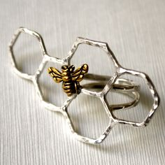 The Sterling Silver Honey Knuckles Ring is a striking and unique piece. This handmade accessory is made from sterling silver and features a striking honeycomb design with a gold plated bee. The design also features a comfortable double-shanked band. Since each one is handcrafted, no two are alike. This is a standout gift for jewelry lovers in your life.