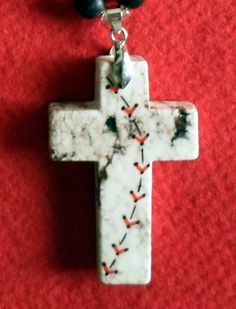 """This necklace is hand strung using 8mm black tourquoise howlite rounds separated with glass, silver linned seeds. The pendant is a beautiful marble cross, hand painted approx. 45mm. Necklace is approx. 16"""" long as is but can easily be extended up to 20""""."""