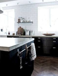 Cement countertops, herringbone floors, black cabinetry, no upper cabinetry