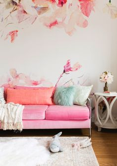 Feminine living space with floral wallpaper, and pink couch