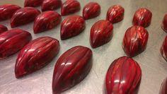 Bonbons van pure chocolade (54,5%), gekleurd met rode en witte cacaoboter. Vulling bestaat uit een ganache van tonkabonen op basis van melkchocolade.