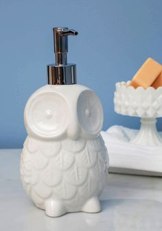 Sink About It Soap Dispenser | Remind your guests to wash up before supper in refreshingly sweet style by perching this owl soap dispenser beside the sink! Featuring subtly contoured features, a polished glaze, and a gleaming silver pump, this white ceramic owl shows that hygiene is a sky-high priority in your enchanting home. Just fill this thoughtful touch with your favorite fragrant soap, and make an everyday chore feel like a true delight.