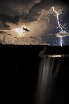 Enlarge this one to get a better view.  Lightning bolt appears to shoot straight through a cloud over the Kaieteur waterfall.  Photo by Robert Harding. Guyana, South America.