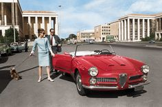 Hepburn with her beloved Yorkie, Mr. Famous, and her first husband, Mel Ferrer, alongside an Alfa Romeo in Rome's Piazza Guglielmo Marconi, circa 1960. FROM REPORTERS ASSOCIATI, DIGITAL COLORIZATION BY LORNA CLARK.