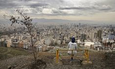 A woman looks out over the city as she observes the ancient festival of Sizdeh Bedar, an annual public picnic day on the day of the Iranian new year. Iranian New Year, Veterinary Services, Tehran Iran, 2017 Photos, The Guardian, High Quality Images, Photo Credit, Concrete, Dolores Park