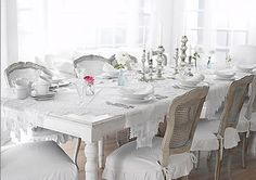 Beautiful table and chairs with the ruffled slip-covered cushions.