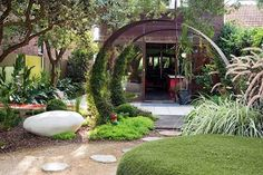 jardin pequeño con sendero de piedras y decoración en arco de hierro