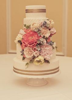 Elegant four tier white wedding cake covered in blush flowers; Featured Photographer: Branham Perceptions Photography