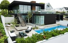 Modern Exterior of Home with picture window, Outdoor lounge chairs, Glass panel railing, Small rock ground cover, Cement wall