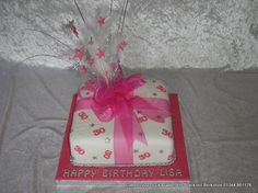 Square single parcel cake with pink sugar numbers and silver stars. Finished with a pink chiffon ribbon and bow and topper with a pink and silver stars topper