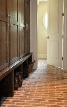 Chicago brick floors. Built in cubbies for each family member. Behind each door there is a hook for coats and backpacks, and each section also has an electrical outlet for laptops, i/pods, and phone chargers. Luxe Living Interiors.