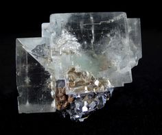 HECK-064  Fluorite and Galena Naica, Chihuahua, Mexico  6.4 x 5.4 x 5.0 cm  Beautifully perched on a cluster of intergrown, lustrous, battleship-gray crystals of galena, are two amazing, almost invisible, glassy and gemmy, pastel-green fluorite crystals. The larger is 5.25 cm in length and both are absolutely stunning for their clarity and under fluorescent light the fluorite exudes a rich purple color.