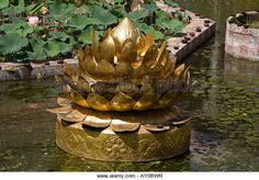 Large golden sculpture of a lotus flower in a pond, Meenakshi Temple, Madurai, Tamil Nadu, India - Stock Image