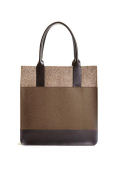 """The Jaunt Tobacco/Ash Tote has proven to be one of our most popular styles season after season. With it's tasteful color blocking pattern and simple architectural structure, this unpretentious shopper adds a graphic element to daily activities. Two interior slip pockets, magnetic snap closure, versatile 8"""" handle drop. Since the beginning, the Jaunt is still being hand crafted by artisans in our LA studio & factory. D Merino wool felt. Genuine leather trim. Two interior pockets. Magnetic…"""