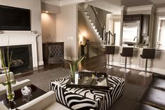 Love this great room space! Square zebra ottoman, dark chocolate tufted chairs, Crate & Barrel gray wool rug, glossy black lacquer able, modern counter bar stools open up to a modern kitchen! Light gray paint wall color. Gray living room. Gray green brown black white brown living room colors.