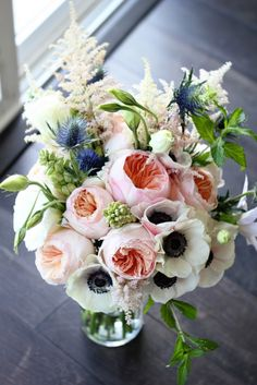garden roses, anemones, pink and whilte astilbe, lisianthus, thistle, and tuberose in bud form, along with a single sprig of mint