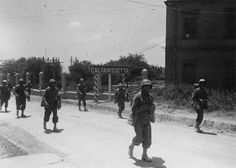 B Company, 179th Infantry Regiment leaving Caltanissetta, Sicily as the 45th Infantry Division drives North to the Coast. Melvin Pederson (with grenade) and Jim Roberts (The man in front). Jim was 1st scout and Melvin was 2nd scout for their squad. 18 July 1943.