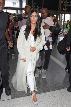 Dressing for comfort but not sacrificing style, she wears an ultra-long cardigan sweater, white tank, distressed white denim, and ankle-tie heels at the airport.   - MarieClaire.com