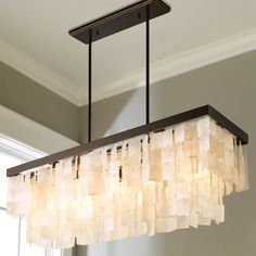 This sleek modern chandelier surrounds a five light cluster with a thin metal drum shade. The Matte Black shade has a metallic Copper interior and seems to float around the fixture due to subtle wire suspensions. Capiz Shell Chandelier, Mobile Chandelier, Rectangle Chandelier, Bronze Chandelier, Linear Chandelier, Chandelier Shades, Chandelier Lighting, Chandeliers, Beach Chandelier