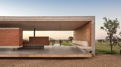 Concrete ribs extend across the brickwork walls of this house on the outskirts of Brasília, Brazil, which Bloco Arquitetos has designed as a two pavilions linked by an outdoor path.