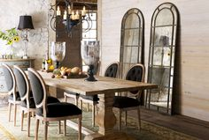 Rustic & Refined. Pale natural wood contrasts with black linen and a graceful iron chandelier in this dining room. Arched mirrors reflect light and create the illusion of more windows.