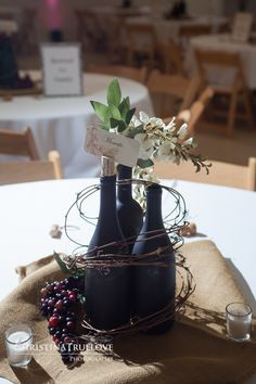 Love this wine bottles, grapes and twig centerpiece idea for a wine themed wedding!