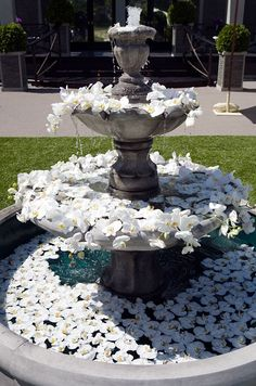 An ornate fountain overflows with hundreds of white orchids.