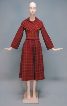 Wool plaid suit, multi hue windowpane pattern trimmed in gold suede, jacket having shawl collar crossing at front or back into a rear buckle, hidden brass snaps, matching A-line skirt with wide waistband and side zipper, lined in orange satin, jacket unlined, Bonnie Cashin, 1967