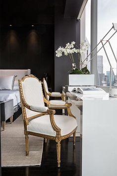Chic contemporary bedroom features a black wall lined with a white wingback bed dressed in white and platinum gray duvet & shams alongside a gray velvet bench placed at the foot of the bed situated across from side by side white lacquered desks and white and gold French chairs placed in front of windows.