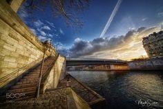 Secret light - The Saint-Louis Bridge and the Ile de la Cité with the rising sun behind the buildings seen from the banks of the Seine.